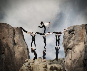 Extraordinary Team Work Of People Filling A Gap In A Cliff