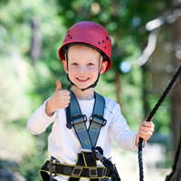 Little Boy In His Harness And Helmet Showing A Thumbs Up